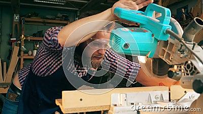 De roterende zaag went aan gesneden hout door de timmerman stock footage