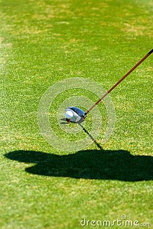 De schaduw van de golfspeler terwijl het voorbereidingen treffen te zetten