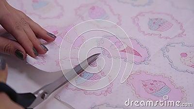 De scharen snijden de stof met een helder en kleurrijk patroon Sluiten stock footage