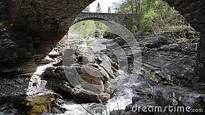 De Schotse brug van toeristische attractieinvermoriston die door Thomas Telford in 1813 wordt gebouwd de Rivier Moriston te kruis stock videobeelden