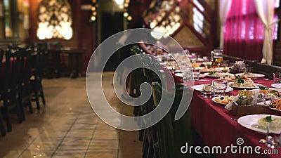 De serveerster schikt platen van voedsel op lijst in restaurant voor collectief diner, die zaal banqueting stock videobeelden