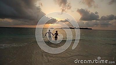 De silhouetten van jong gelukkig paar die aan zonsondergang in oceaanholding lopen dient langzame motie in Twee minnaars op witte stock videobeelden