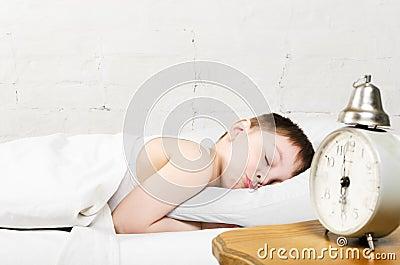 De slaap van de jongen in bed