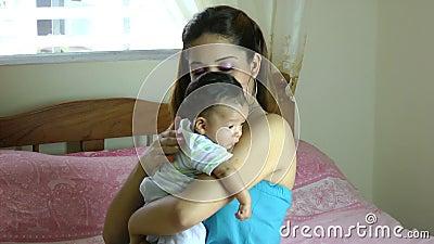 De Spaanse de moederholding van Latina het kwijlen baby over schouder en het onttrekken op rug zodat zuigeling kan boeren stock videobeelden