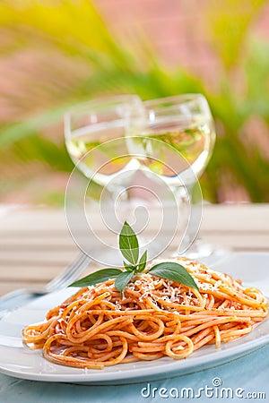 De spaghetti met tomatensaus en twee glazen van winnen