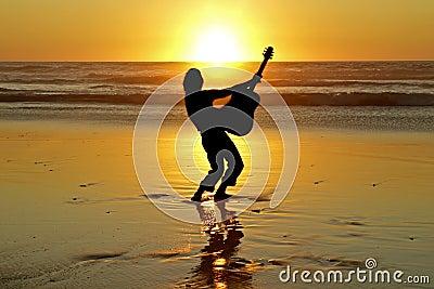 De speler van de gitaar op het strand