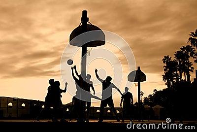 De spelers van het basketbal bij zonsondergang