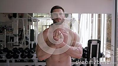 De spierbodybuilder naakt-chested met atletisch lichaam vóór spiegel en warmt vóór machtstraining op bij sporten stock videobeelden