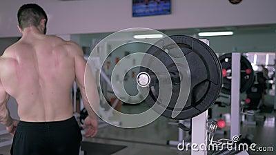 De sportclub, spier naakt-chested bodybuilder legt schijf op barbell aan bankpers die tijdens voor sportensterkte binnen opleiden stock video
