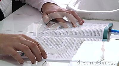 De student doorbladert het handboek stock video