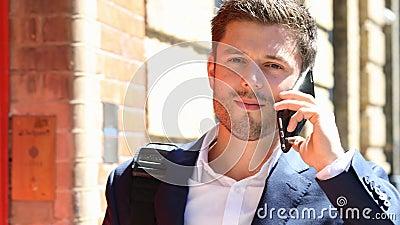 De Telefoon die van zakenmantalking on mobile langs Stadsstraat lopen stock videobeelden