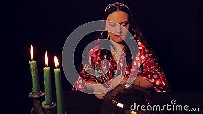 De teller van het zigeunerfortuin bij de lijst door kaarslicht spreidt fortunetelling kaarten uit stock videobeelden