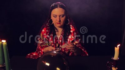 De teller van het zigeunerfortuin bij de lijst schuifelt fortunetelling kaarten stock video