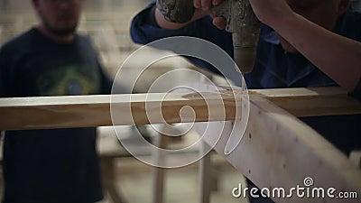 De timmerlieden boren een gat en maken een schroef met een schroevedraaier vast stock footage