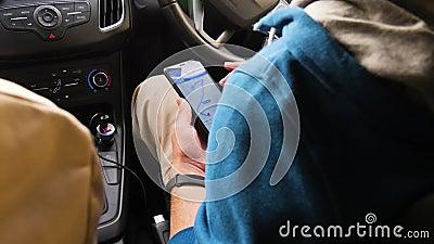 De toeristen kiezen de richting op de kaart in de telefoon De man zoekt een bestemming, zittend in de auto E stock footage