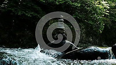 De toren of de steenhoop bevinden zich op een kei in een bergrivier, langzame motie stock video