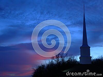 De torenspits van de kerk bij zonsondergang