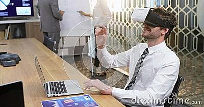 De uitvoerende macht die virtuele werkelijkheidshoofdtelefoon met behulp van terwijl collega's die over tikgrafiek 4k bespreken stock footage