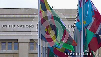 De V.N.-de vlaggen die van lidstaten dichtbij het Bureau van de Verenigde Naties in Genève, Zwitserland vliegen stock videobeelden
