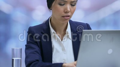 De vermoeide werknemer die van het damebureau aan sterke hoofdpijn lijden en laptop, spanning sluiten stock video