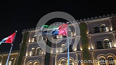 De vlag van de Verenigde Arabische Emiraten zwaait 's nachts naast het landmerk Al Qasba in Sharjah stock video