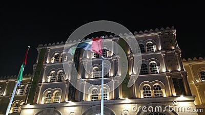 De vlag van de Verenigde Arabische Emiraten zwaait 's nachts naast het landmerk Al Qasba in Sharjah stock footage