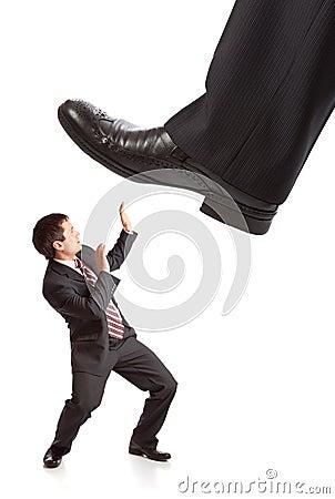 De voet die van de zakenman op uiterst kleine zakenman stapt