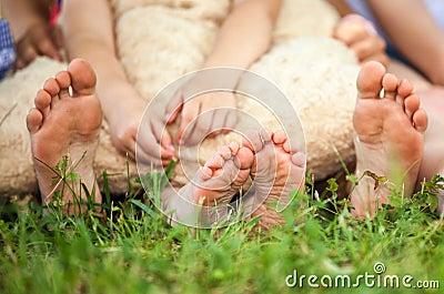 De voeten van kinderen op een gras