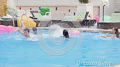 De vrienden bij de jeugd van de de zomerpartij hebben pret in blauw water en maken plonsen in zwembad stock video