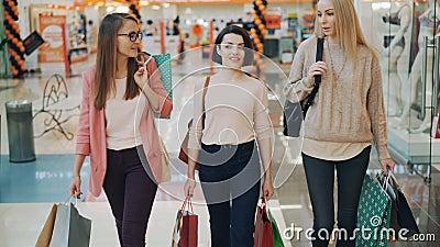 De vrij jonge vrouwen spreken terwijl het lopen in winkelcomplex dragende document zakken met aankopen Kleinhandels, gelukkig stock footage