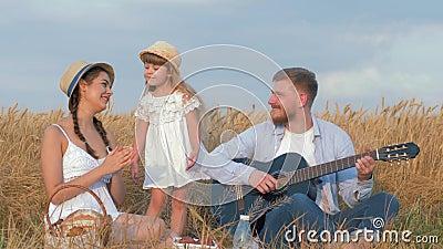De vrolijke familieuitjes, vader speelt koord muzikaal instrument terwijl het mamma haar handen slaat en weinig dochter binnen da stock videobeelden