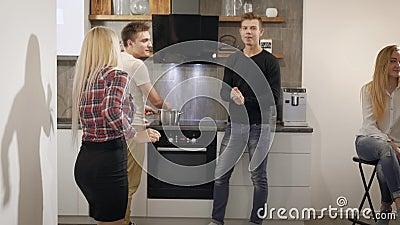 De vrolijke tieners en de meisjes hebben pret op een keuken in flat in avond, drinkend wijn stock videobeelden