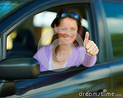 De vrouw die duimen toont ondertekent omhoog in auto