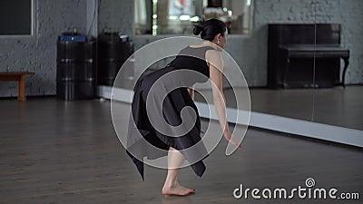 De vrouw in kleding maakt saldo op haar been in langzame motie stock videobeelden