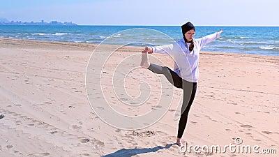 De vrouw maakt yoga op overzees strand opheft haar been en houdt het saldo stelt indient stock video