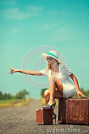 De vrouw met koffer houdt de auto tegen