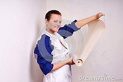 De vrouw probeert op behang aan muur