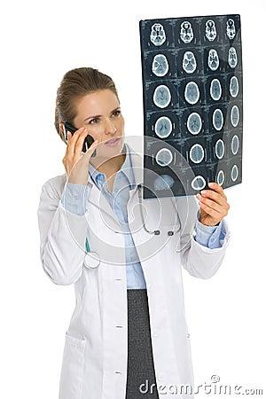 De vrouw van de arts het spreken telefoon en het kijken op MRI