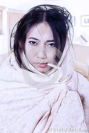 De vrouw van de koorts met thermometer die in deken wordt verpakt