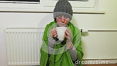 De vrouw verwarmt dichtbij het verwarmen van radiator en drinkt thee stock videobeelden