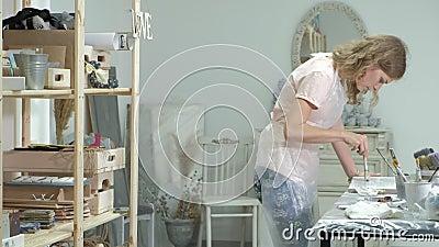 De vrouw in de workshop werkt aan houten raad, die een effect van antiquiteit creëren stock videobeelden