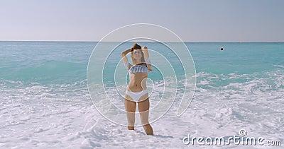 De vrouw zorgeloos op het beatige strand Het meisje is ontspannen en laat vreugde en geluk zien in het dunne lichaam voor een die stock video