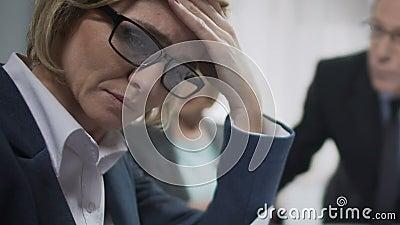 De vrouwelijke die beambte op conferentie wordt verstoord, voelt hoofdpijn, boze ongeveer ontbreekt de werkgever stock videobeelden