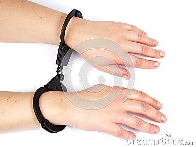 De vrouwelijke handen shackled in handboeien