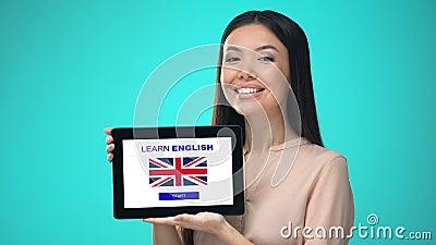 De vrouwelijke holdingstablet met leert Britse Engelse toepassing, klaar te beginnen stock video