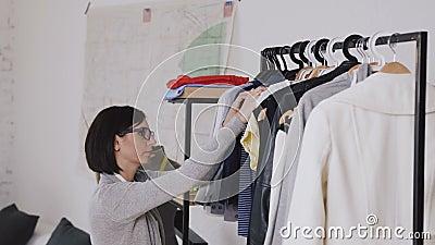 De vrouwelijke manierontwerper werkt bij de nieuwe inzameling voor cliënten in comfortabele workshopstudio, naaister, kleermaker  stock footage