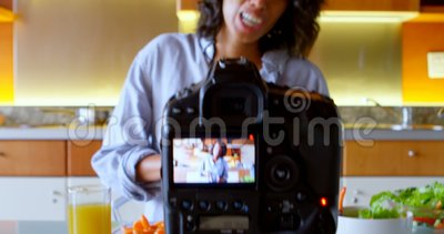 De vrouwelijke video van de bloggeropname terwijl het snijden van plak van wortel in keuken 4k stock video