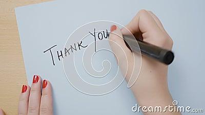 De vrouwenhanden met het rode nagellak schrijven danken u op een blauw document met een zwarte teller - stock videobeelden