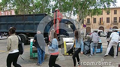 De vuilnismannen op een grote vrachtwagen verzamelen gesorteerd afval van containers in het centrum van de stad stock footage