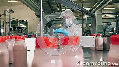 De werknemer van de fabriek verwijdert defecte melkflessen stock videobeelden